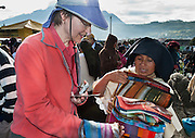 A tourist negotiates with a fabric seller at a market in Otavalo, Ecuador, South America. The culturally vibrant town of Otavalo attracts many tourists to a valley of the Imbabura Province of Ecuador, surrounded by the peaks of Imbabura 4,610m, Cotacachi 4,995m, and Mojanda volcanoes. The indigenous Otavaleños are famous for weaving textiles, usually made of wool, which are sold at the famous Saturday market and smaller markets during the rest of the week. The Plaza del Ponchos and many shops tantalize buyers with a wide array of handicrafts. Nearby villages and towns are also famous for particular crafts: Cotacachi, the center of Ecuador's leather industry, is known for its polished calf skins; and San Antonio specializes in wood carving of statues, picture frames and furniture. Otavaliña women traditionally wear distinctive white embroidered blouses, with flared lace sleeves, and black or dark over skirts, with cream or white under skirts. Long hair is tied back with a 3cm band of woven multi colored material, often matching the band which is wound several times around their waists. They usually have many strings of gold beads around their necks, and matching tightly wound long strings of coral beads around each wrist. Men wear white trousers, and dark blue ponchos. Otavalo is also known for its Inca-influenced traditional music (sometimes known as Andean New Age) and musicians who travel around the world. For licensing options, please inquire.