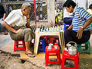 16 JUNE 2013 - YANGON, MYANMAR:  Men play chess on the street in Yangon. Yangon, formerly Rangoon, is the largest city in Myanmar. It is the former capital of the Southeast Asian country. It's still Myanmar's economic capital.      PHOTO BY JACK KURTZ