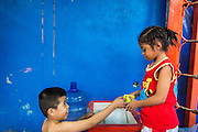 23 DECEMBER 2014 - BANGKOK, THAILAND: A boy boxer hands a cup of water to BAI THONG, 7 years old, after they worked out at the Kanisorn gym in Bangkok. She has been boxing for about 5 months. The Kanisorn boxing gym is a small gym along the Wong Wian Yai - Samut Sakhon train tracks. Young people from the nearby communities come to the gym to learn Thai boxing. Muay Thai (Muai Thai) is a mixed martial art developed in Thailand. Muay Thai became widespread internationally in the twentieth century, when Thai boxers defeated other well known boxers. A professional league is governed by the World Muay Thai Council. Muay Thai is frequently seen as a way out of poverty for young Thais. Muay Thai professionals and champions are often celebrities in Thailand.     PHOTO BY JACK KURTZ