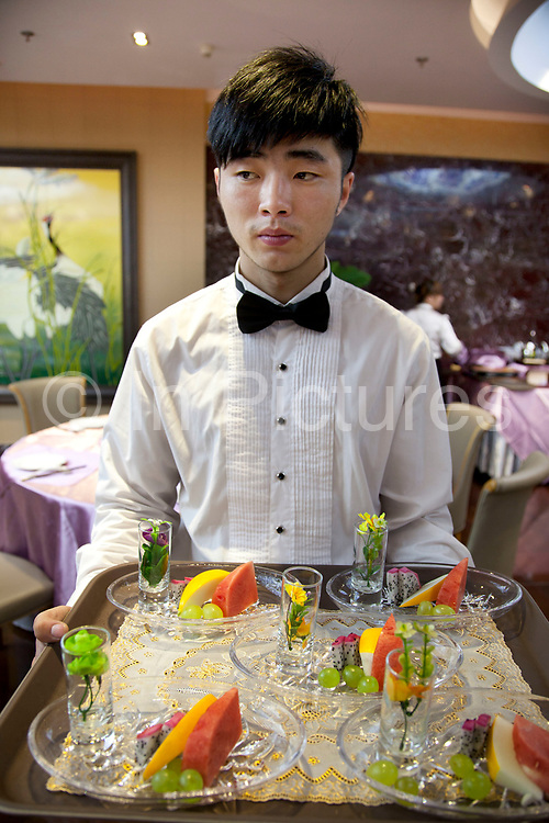 A waiter brings the cleansing fruit desert into the dining room. Quanjude roast duck restaurant in Wangfujing, Beijing. This is a Chinese restaurant known for its trademark Peking Roast Duck and is known for being the best roast duck restaurant in China. Quanjude was established in 1864 during the Qing Dynasty under the reign of the Tongzhi Emperor. Although Peking Duck can trace its history many centuries back, Quanjude's heritage of roast duck preparation - using open ovens and non-smoky hardwood fuel such as Chinese date, peach, or pear to add a subtle fruity flavor with a golden crisp to the skin, was originally reserved for the imperial families.