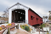 """Bridgeton Historic District, Indiana: Bridgeton Covered Bridge (245 feet long) was rebuilt in historically accurate Burr Arch style in 2006 over Big Raccoon Creek (replacing 1868 bridge burnt by arson in 2005) on Bridgeton Road, Parke County, Indiana, USA. Bridgeton Mill was established 1823, rebuilt 1870, and is the oldest continuously operating mill west of the Allegheny Mountains. The mill grinds wheat into flour and corn into meal with 200 year-old French Buhr stones. Red and white paint protects the wood bridge. The traditional """"Cross this bridge at a walk"""" sign required slow vehicle speed, but traffic is now diverted to an adjacent modern bridge."""