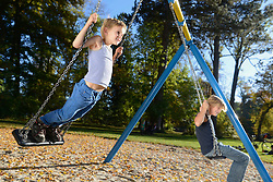 Boys swinging on swing in playground, Bavaria, Germany