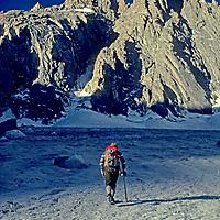 MOUNTAINEERING. Climber crossing Palisade Glacier below 14,242' North Palisade Peak, John Muir Wilderness, Sierra Nevada, CA.