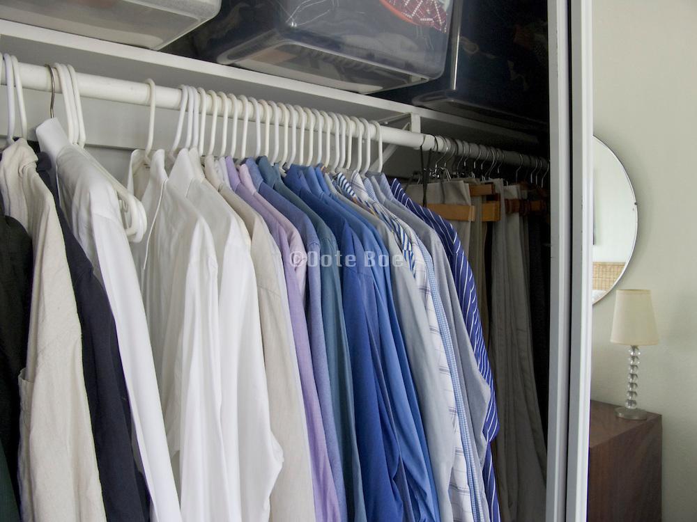men shirts and pants hanging in a closet