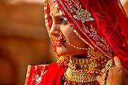 A young girl wearing a traditional bridal outfit at the Desert Festival on 29th January 2018  in Jaisalmer, Rajasthan, India. It is an annual event that take place in February. The bridal dowry is a rich aray of silver and gold jewelry and the hands and arms are adorned with henna patterns.