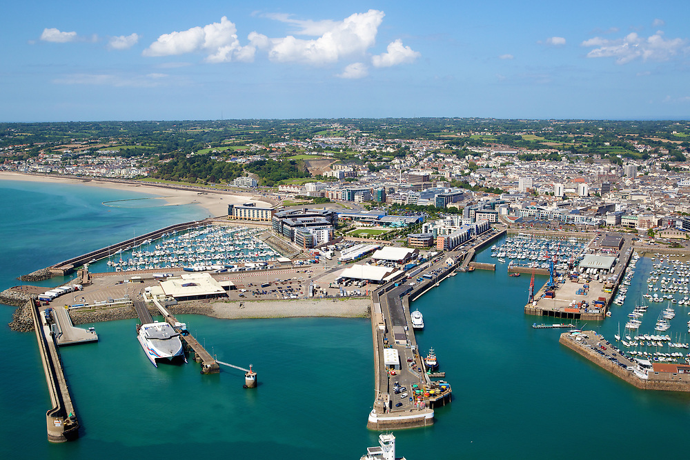Aerial view of the boats moored up at St Helier harbour and St Aubin's Bay in the distance on a a calm, sunny day in Jersey, Channel Islands
