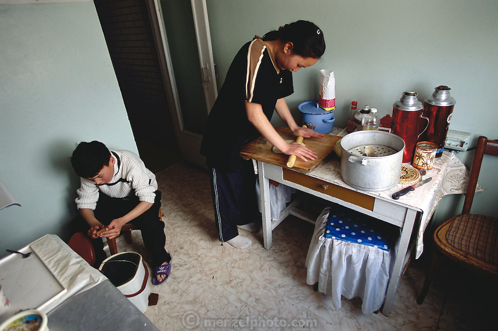 (MODEL RELEASED IMAGE). Khorloo Batsuuri rolls out dough for their family's dinner of buuz (mutton-stuffed dumplings) in the small kitchen of her Mongolian home which her family of four shares with two other families. Batbileg is peeling potatoes nearby. (Supporting image from the project Hungry Planet: What the World Eats.) The Batsuuri family of Ulaanbaatar, Mongolia, is one of the thirty families featured, with a weeks' worth of food, in the book Hungry Planet: What the World Eats.