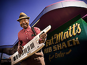 An elderly african-american blues musician stands with a big smile playing his keytar in front of an Atlanta restaurant.