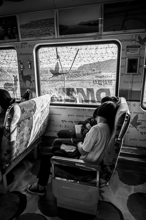 A the end of a tour of the Korean DMZ, tired passengers aboard the DMZ Peace Train nap as it exits the heavily fortified DMZ bound for Seoul Station. (September 29, 2019)