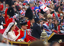 Prince William and his bride Kate make their way down The Mall in London in the procession to Buckingham Palace after the wedding ceremony.