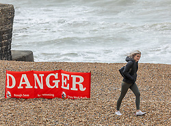 Licensed to London News Pictures. 04/05/2021. Brighton, UK. A women walks past a No Swimming warning sign on Brighton beach East Sussex as high winds continue to batter the UK this morning. Today, the Met Office have issued weather warnings across the South of England for stormy weather with winds speeds expected to reach up to 50mph again. Photo credit: Alex Lentati/LNP