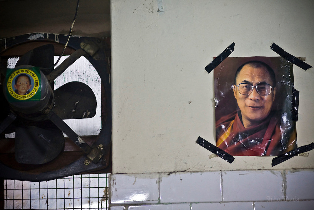 """INDIA - Life in Exile (Tibetan Refugees) <br /> A picture of Dalai Lama, right, and """"Free Panchen Lama"""" campaign sticker are seen at reception center, a temporary shelter for newly arrived Tibetan refugees in McLeod Ganj, Dharamsala, India, where the Dalai Lama settled after fleeing Tibet in 1959 after a failed uprising against Chinese rule, May 29, 2009.  The 11th incarnation of the Panchen Lama, Gedhun Choekyi Nyima, was taken custody by Chinese authorities and vanished from public eyes shortly after being named by Dalai Lama in 1995."""