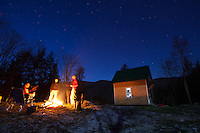 A group of people hanging around a campfire at twilight in northern Vermont