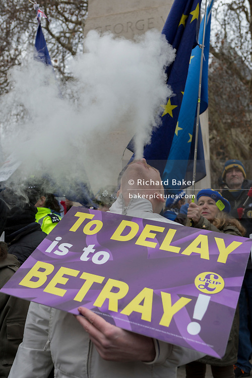 On the day that the UK Parliament once again votes on an amendment of Prime Minister Theresa May's Brexit deal that requires another negotiation with the EU in Brussels, a far-right pro-Remain vapes among pro-EU protesters gather outside the House of Commons, on 29th January 2019, in Westminster, London, England.