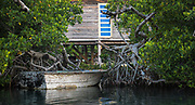 Old vessels line the mangrove channels that weave through Ambergious Caye in Belize
