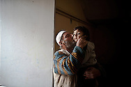 Jamil Wasif kisses his grandson Jamil as they wait for the rain to stop. Yayladagi refugee camp for Syrians in southern Turkey. 12/21/2012 Bradley Secker for the Washington Post