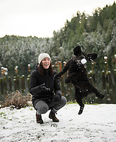 Marley the cocker spaniel catches a snowball at Tod Inlet, part of Gowlland Tod Provincial Park near Victoria, BC as Taylor looks on!