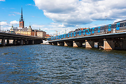 Train on railway bridge in city, Gamla Stan, Stockholm, Sweden