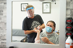 ©Licensed to London News Pictures 04/07/2020     <br /> Petts Wood, UK. A customer being given hand sanitiser. Mr Snips hair studio and Barber shop in Petts Wood high street, Petts Wood, South East London, has reopened today after three months of coronavirus lockdown. Staff and customers have to wear PPE. Photo credit: Grant Falvey/LNP