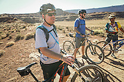 SHOT 10/16/16 3:46:08 PM - Tom Reynolds of Denver, Co. pauses with other riders in the group to take in the view along the White Rim Trail. The White Rim is a mountain biking trip in Canyonlands National Park just outside of Moab, Utah. The White Rim Road is a 71.2-mile-long unpaved four-wheel drive road that traverses the top of the White Rim Sandstone formation below the Island in the Sky mesa of Canyonlands National Park in southern Utah in the United States. The road was constructed in the 1950s by the Atomic Energy Commission to provide access for individual prospectors intent on mining uranium deposits for use in nuclear weapons production during the Cold War. Four-wheel drive vehicles and mountain bikes are the most common modes of transport though horseback riding and hiking are also permitted.<br /> (Photo by Marc Piscotty / © 2016)