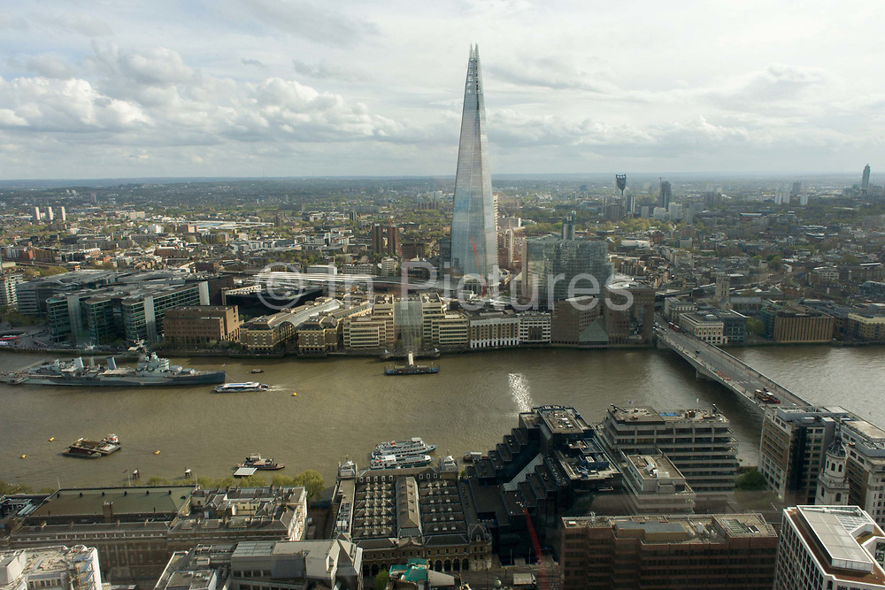 River Thames and southbank London skyline (The Shard, right) seen from the Sky Garden of the Walkie Talkie building in the City of London. The panoramic cityscape shows the modern metropolis looking southwards, from the northern bank of the river to the southern where the borough of Southwark starts, continuing into the distance. On the river is the WW2 battleship museum HMS Belfast and London Bridge, a crossing since the Roman wooden bridge from the 1st century. The Shard is an 87-storey skyscraper standing 306 metres (1,004 ft) high.