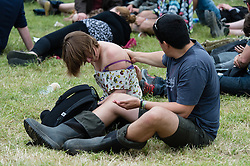 © Licensed to London News Pictures. 26/06/2015. Pilton, UK.  Festival atmosphere at Glastonbury Festival 2015 on Friday Day 3 of the festival.  A man rubs sun lotion on his partners back - yesterday was hot and sunny, while today is overcast with showers.  This years headline acts include Kanye West, The Who and Florence and the Machine, the latter being upgraded in the bill to replace original headline act Foo Fighters.   Photo credit: Richard Isaac/LNP