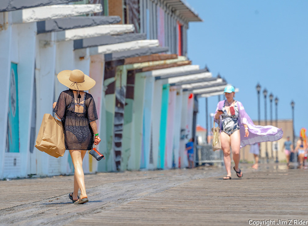 A woman strolls by mid-century retail spaces along the boardwalk that are in need of restoration.