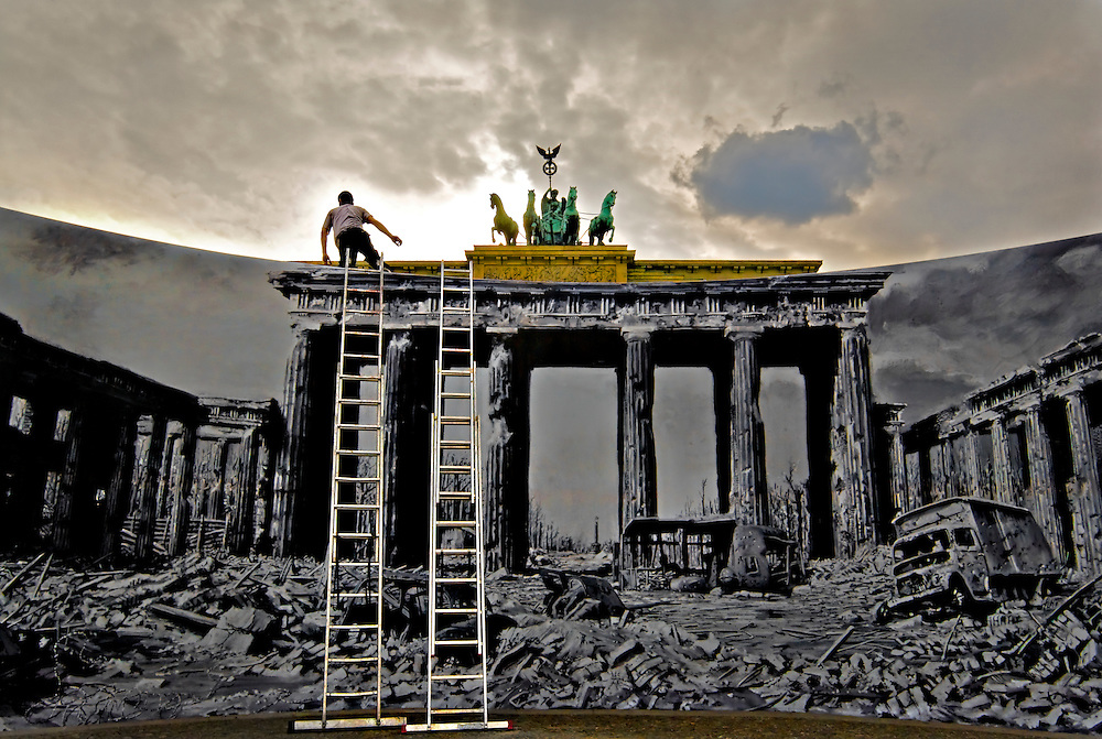 Brandenburgertor, Berlin. 60 anniversary of the ending of WW2.  A man climbs a latter in front of a large painting showing the destroyed Pariser Platz after World War II.
