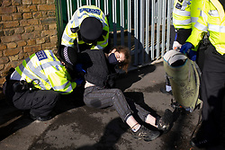 © Licensed to London News Pictures. 04/10/2021. London, UK. An arrested activist from Insulate Britain has her handcuffs adjusted at the entrance to the Blackwall tunnel after the group blocked the tunnel earlier this morning. Insulate Britain have successfully blocked various roads around the capital over a number of weeks, resulting in a court injunction banning them from going near the M25 motorway.  Photo credit: George Cracknell Wright/LNP