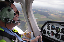 Man with disability; who is wheelchair user; sitting in aircraft cockpit; wearing earphones and mouthpiece; flying plane,