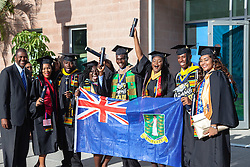 Graduates pose with the BVI flag of Sierra Scatliffe.  Fifty-first annual University of the Virgin Islands  Commencement Exercises.  UVI Sports & Fitness Center.  St. Thomas, VI.  14 May 2015.  © Aisha-Zakiya Boyd