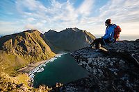 Female hiker enjoying view of Kvalvika beach from near summit of Ryten, Moskenesoy, Lofoten Islands, Norway