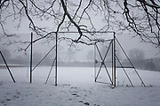 A landscape of bleak mid-winter in a city park. A football pitch is seen snowbound and empty, its gates sgtill open and bare branches of trees hang low. During a prolonged cold spell of bad weather, snow fell continuously on the capital days before, allowing families the chance to enjoy the bleak conditions in Ruskin Park in the borough of Lambeth.