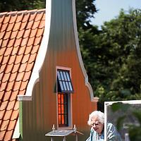 Nederland, Zaandam , 5 juli 2013.<br /> Wandeling door de binnenstad van Zaandam.<br /> Starten bij De Werf aan de Oostzijde. Daarvandaan kun je lopen op een soort boulevard tussen de flats en het water. De eerste stop is De Fabriek, filmhuis en eetcafé met terras aan de Zaan met uitzicht op de sluis. Daarna de sluis zelf.<br /> Dan langs het winkelgebied richting de Koekfabriek: Het oude Verkade pand dat is verbouwd en waar nu de bieb en sportschool en restaurant etc. in zitten.<br /> (Dat is aan de overkant van het startpunt) en misschien nog de Zwaardemaker meepakken aan de Oostzijde. Dat is een oud pakhuis die Rochdale enige jaren geleden heeft verbouwt tot appartementen met een stukje Nieuwbouw.<br /> Ook doen: het Russische buurtje vlakbij de Zaan. Dit jaar staat Rusland in de schijnwerpers en Zaandam heeft een speciale band met Rusland, vanwege het Czaar Peterhuisje en de Russische buurt. <br /> Op de foto: Oude Zaandamse vrouw vasnaf haar balkon aan de Hogendijk met op de achtergrond  huizen in Zaanse stijl.<br /> Foto:Jean-Pierre Jans