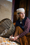 An elderly woman picks kernels off of dried corn cobs at her home in Landruk, Annapurna Himalaya, Nepal.