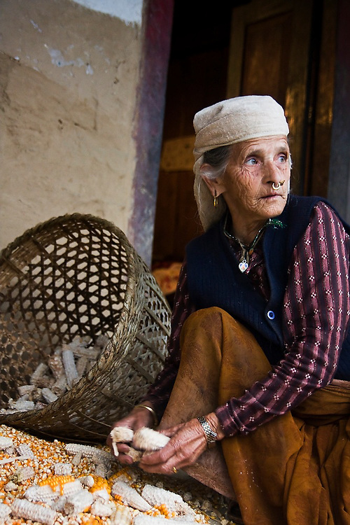 An elderly woman picks kernels off of dried corn cobs at her home in Landruk, Annapurna Himalaya, Nepal.