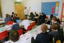 Secondary school teacher in classroom with pupils,