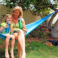 A mother and daughter share values of healthy green living drinking water from reusable refilable water bottles.