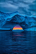 Midnight sun peers through an artistically carved iceberg formation in the icy waters of the Arctic Ocean.