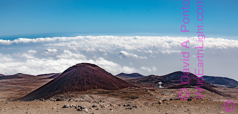 Very Long Baseline Array (Mauna Kea site)  radio telescope seems  isolated in the volcanic landscape near the summit of Mauna Kea, Big Island, Hawaii.  Looking down from near the top of Mauna Kea, the cloud layers below show an evident transition to the cold dry air at high altitude. © David A. Ponton