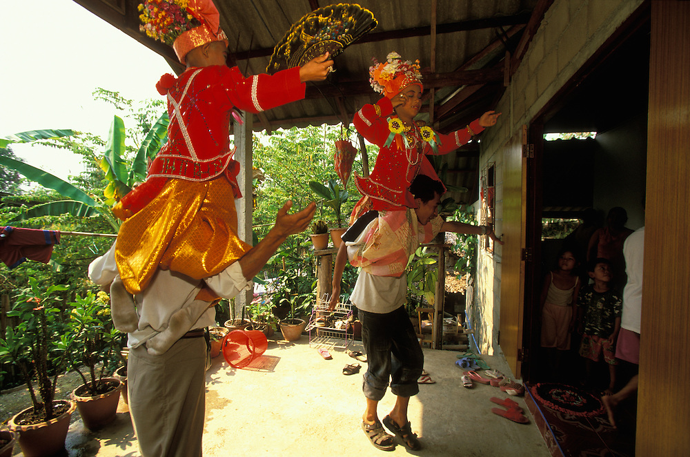 Attendants dance with boys dressed up as princes on their shoulders while they approach the house of some relatives during Poy Sang Long, the yearly ordination of novice monks, Mae Hong Son, Thailand.