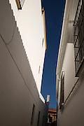 Deep blue sky narrow alley whitewashed buildings, Barrio de Santiago, Jerez de la Frontera, Spain