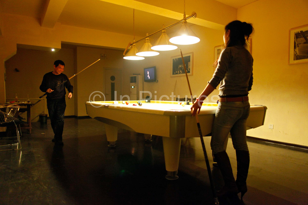 """Patrons play pool at Tony's Bar in Nanjing, China on 04 March, 2011.  Once a mid level executive at a state owned chemical company, Mr. Tony Zhao started the bar for a more interesting life and make """"connections"""" for future business opportunities."""
