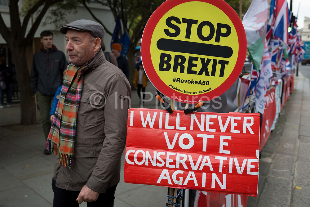 On the day that the EU in Brussels agreed in principle to extend Brexit until 31st January 2020 aka Flextension and not 31st October 2019, a bystander passes a Remainers Stop Brexit, Revoke Artocle 50 lollipop and a Brexiters Ill Never Vote Conservative Again placard during a Brexit protest outside parliament, on 28th October 2019, in Westminster, London, England.