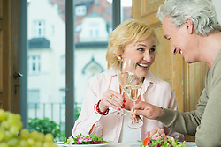 Mature couple sitting at table and clinking glasses of sparkling wine, smiling