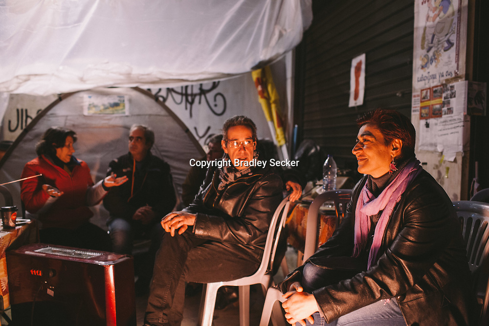 Georgia Ikonomou, 50, (right) sits outside the Ministry of Finance in central Athens. She is one of 595 cleaning ladies made redundant who have protested daily, despite police violence and attacks.