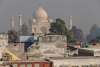 Man pointing a rifle from a building in front of the Taj Mahal