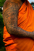Heavily tattoo'd monk in the grounds of Wat Arun: a Buddhist temple (wat) in the Yai district of Bangkok, on the west bank of the Chao Phraya River. Wat Arun is among the best known of Thailand's landmarks. The temple is so named because the first light of the morning reflects off the surface of the temple with pearly iridescence. Although the temple had existed since at least the seventeenth century, its distinctive prang (spires) were built in the early nineteenth century during the reign of King Rama II. Thailand.