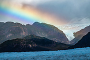 Rainbow over Grey Glacier, Southern Patagonian Ice Field, in Torres del Paine National Park, Chile, Patagonia, South America. Before dividing in two at its tongue, the glacier is 6 kilometers wide and over 30 meters high. Grey Glacier has receded 4 km and lost 17 square kilometers from the mid 1900s through 2010.  Torres del Paine National Park is listed as a World Biosphere Reserve by UNESCO.