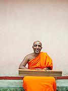 Buddhist monk with religious texts at the Mulkirigala Monastery, Sri Lanka